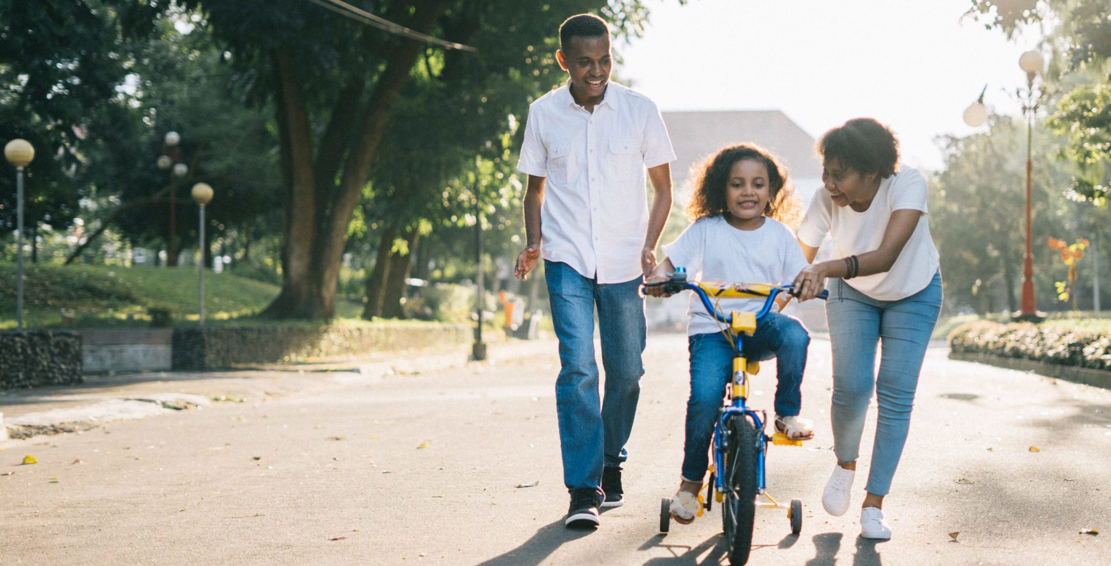 mom and dad teaching child to ride bike