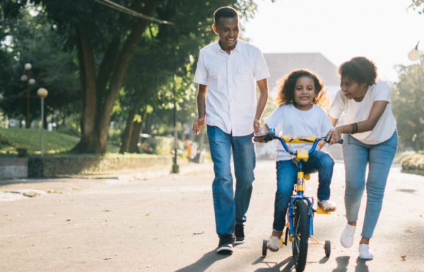 mom and dad teaching child to ride bike outside