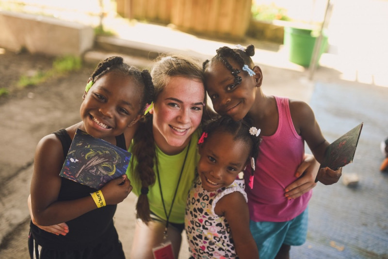 Young girl on mission trip to. Haiti smiling with three young girls with their newly made paintings