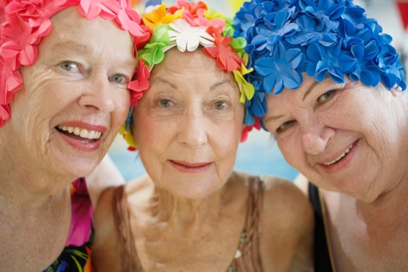 Three elderly women in flowery swim caps smiling for the camera