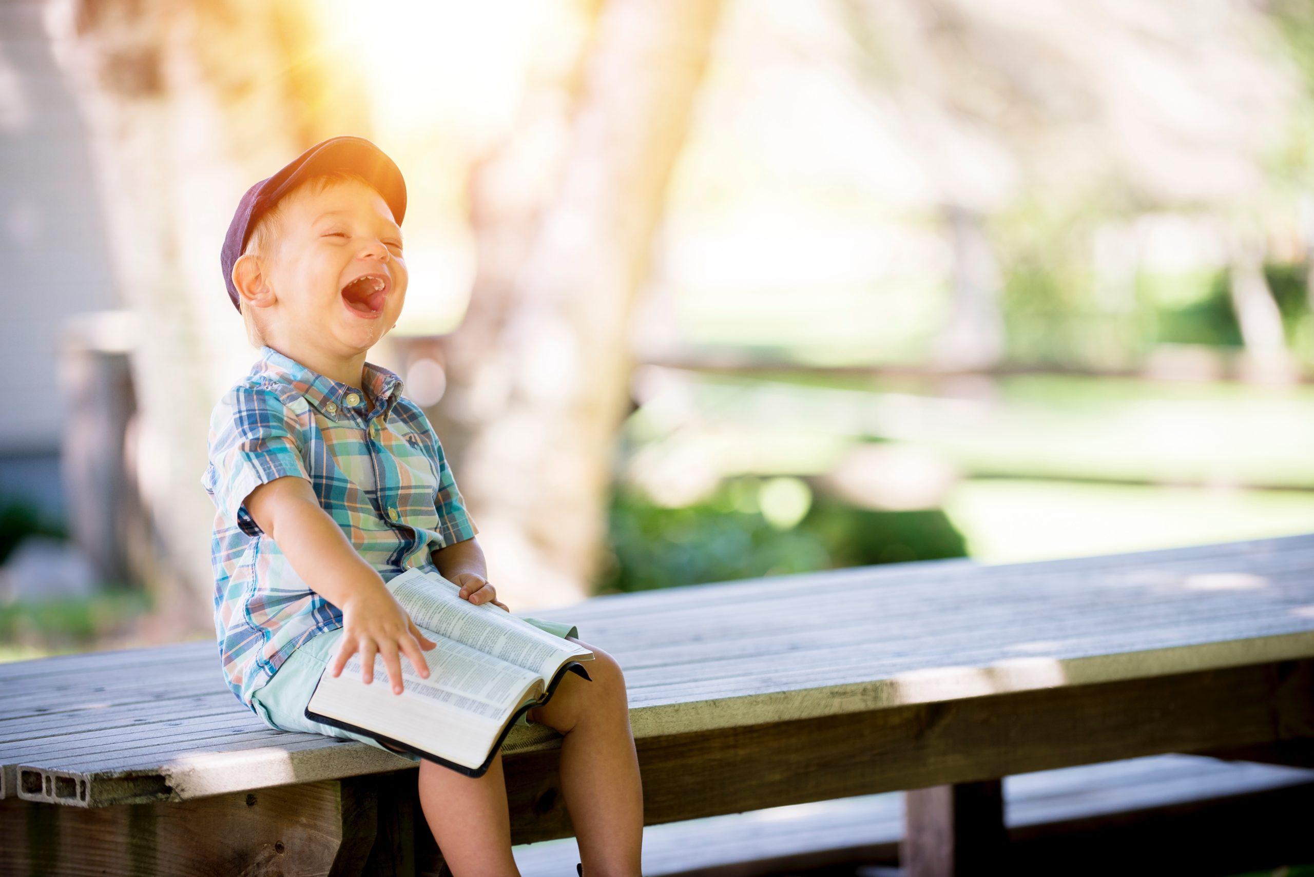 little boy reading outside on a picnic table