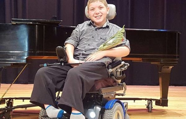 young boy in wheelchair at summer camp holding flowers