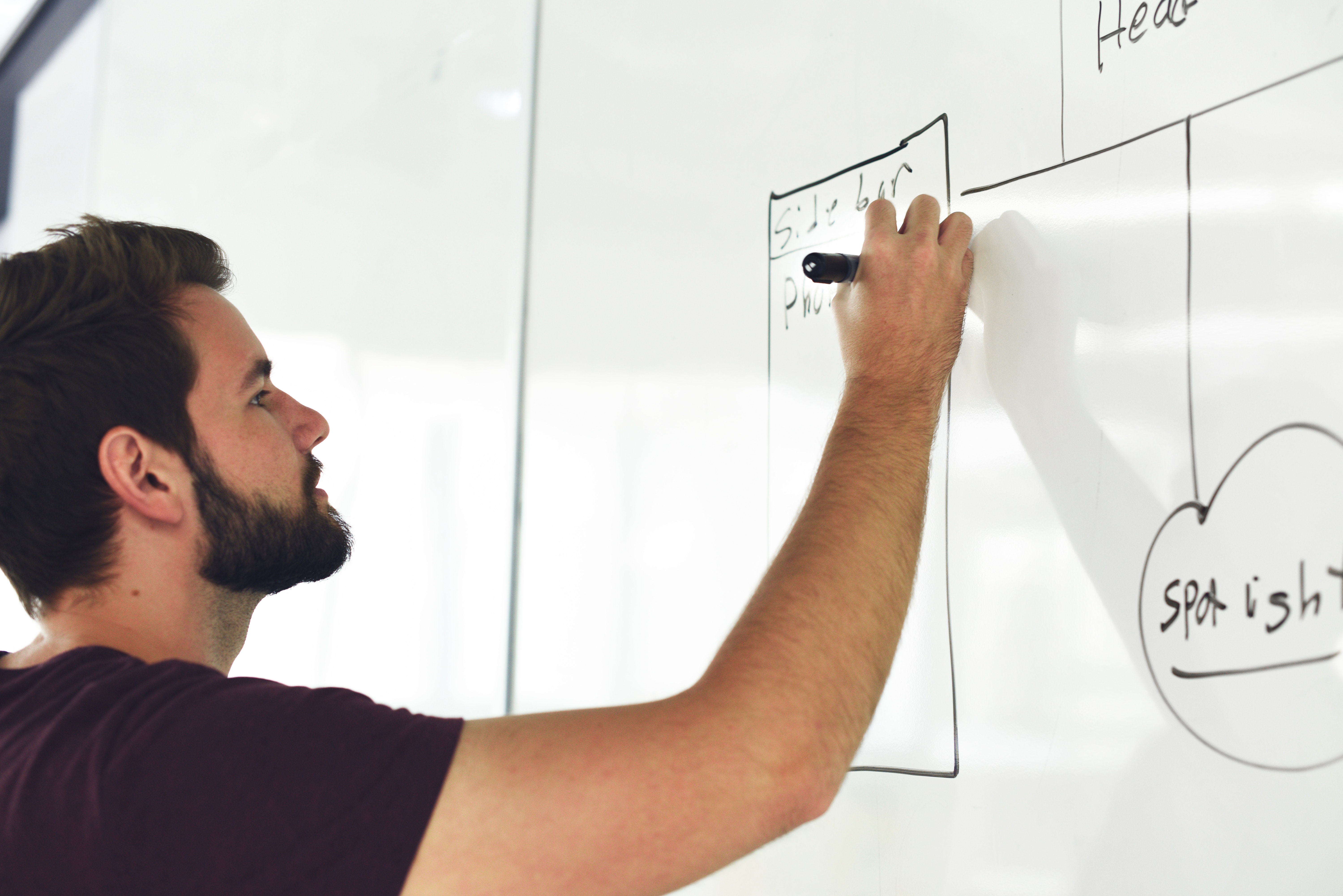 man writing on white board