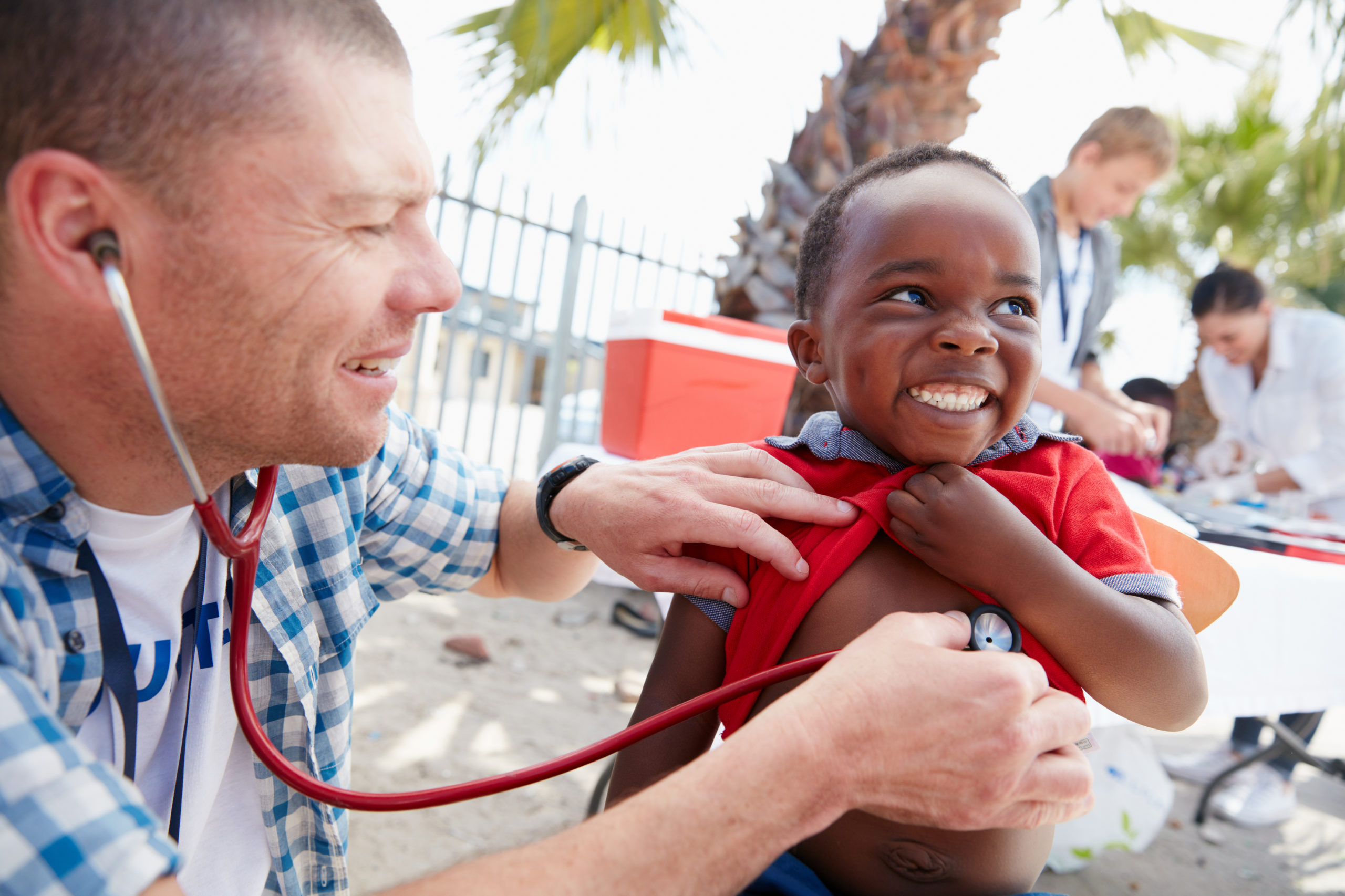 Shot of a volunteer doctor giving checkups to kids