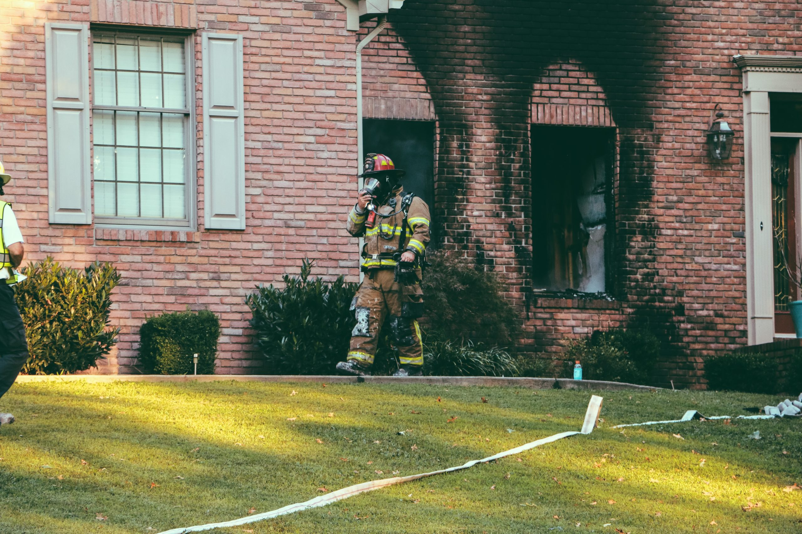 Firefighter walking away from scorched brick building