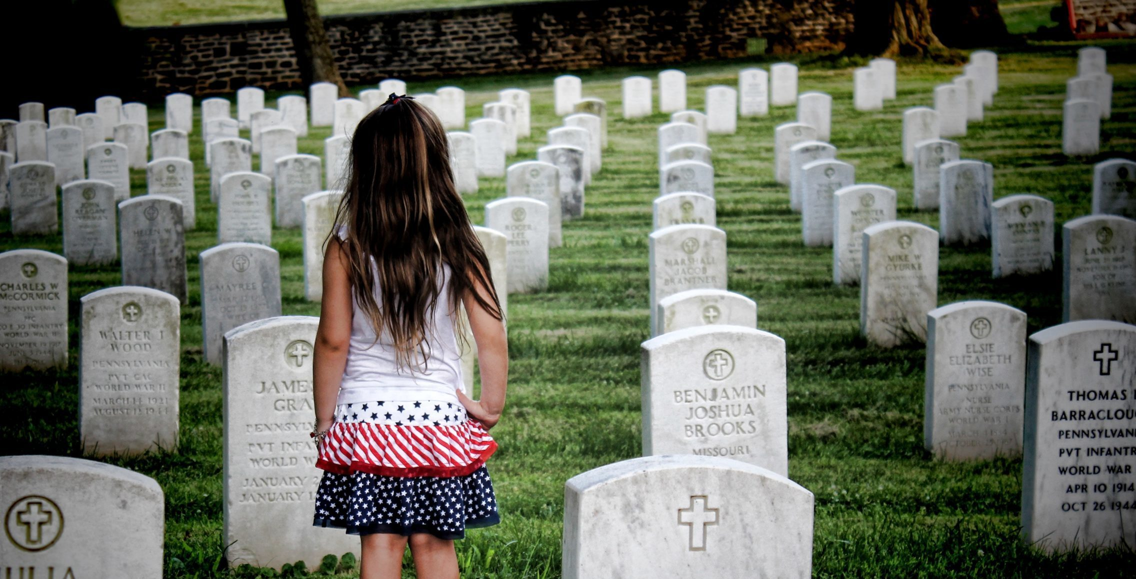 little girl standing by grave