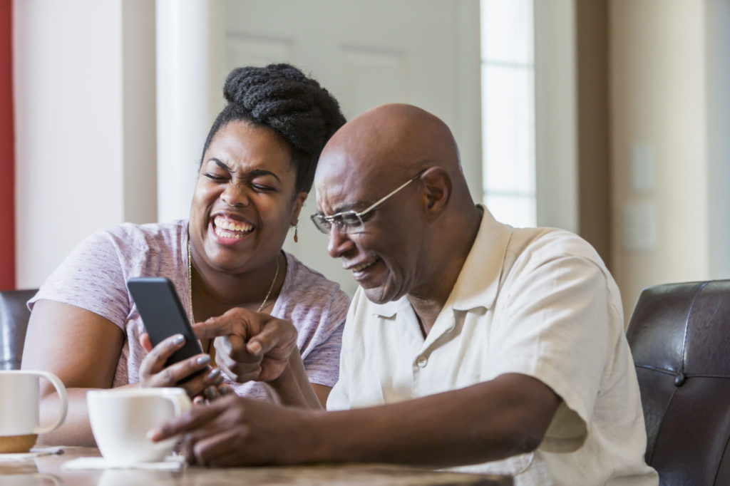 Senior man with adult daughter using smart phone laughing together