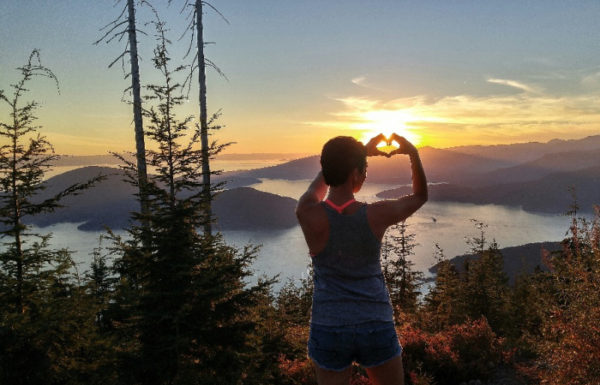 woman hiking making heart with hands over sun