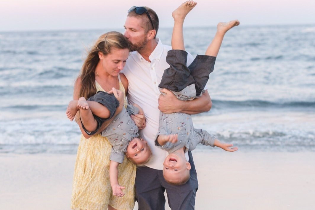 family of four posing for cute photo on beach