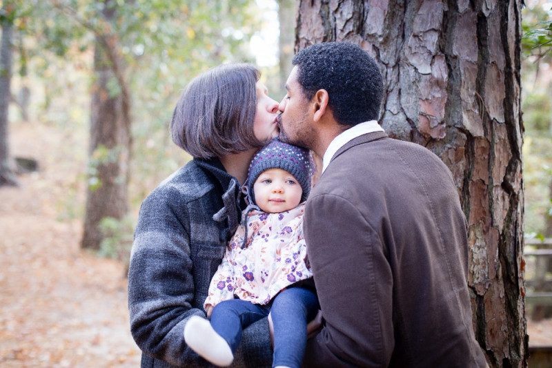 young couple kissing and holding child