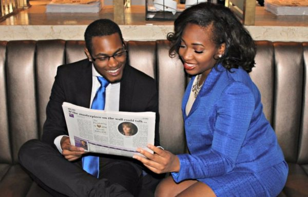 two people reading a newspaper