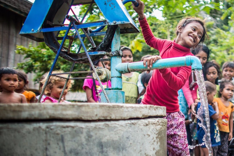 young girl getting water from a well
