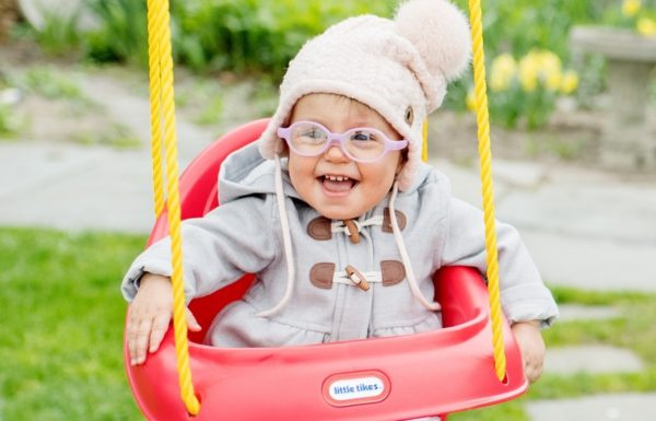 young child in baby swing smiling