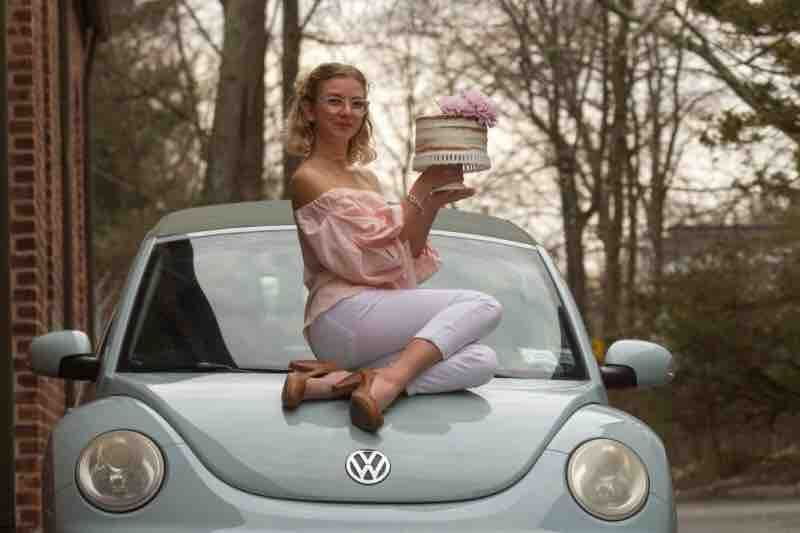 Young woman sitting on car holding a cake