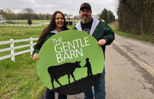 two people holding up sign for the gentle barn