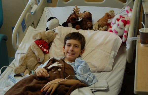 young boy smiling from hospital bed