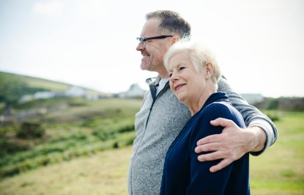 older couple hands over shoulder in embrace