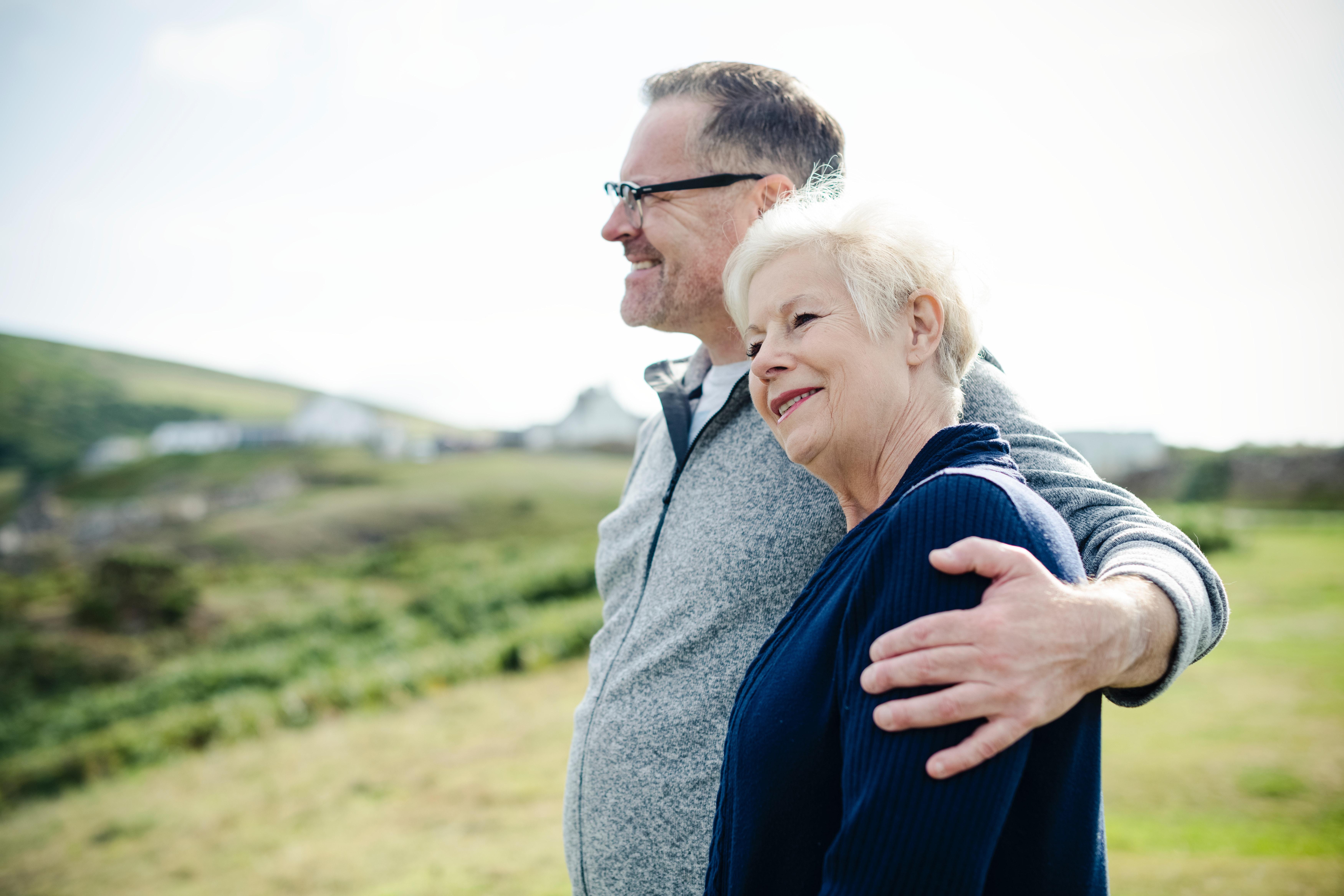 older couple hands over shoulder in embrace