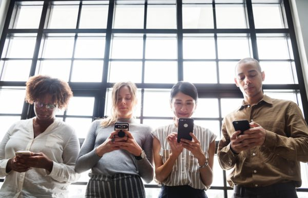 four people on their smartphones typing