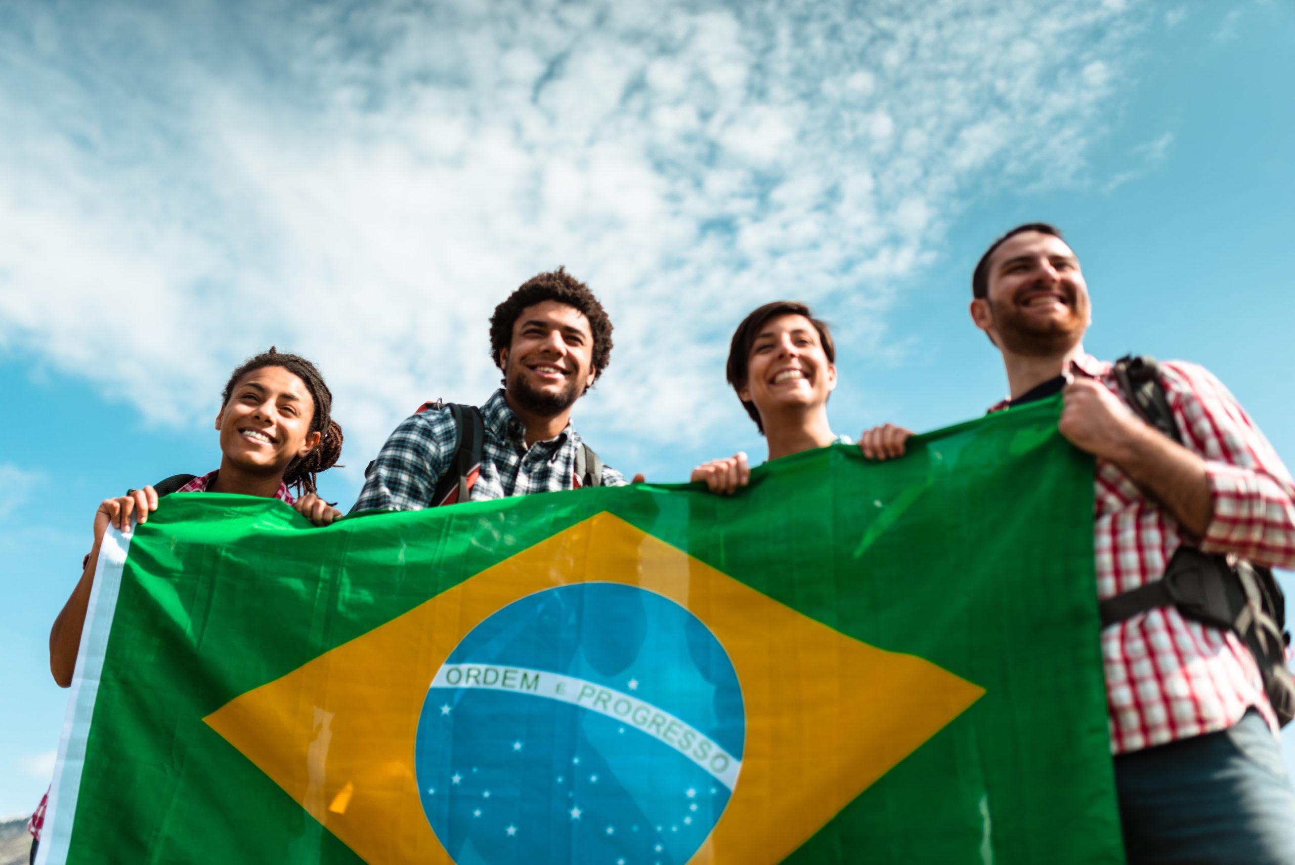 four people holding Brazilian flag