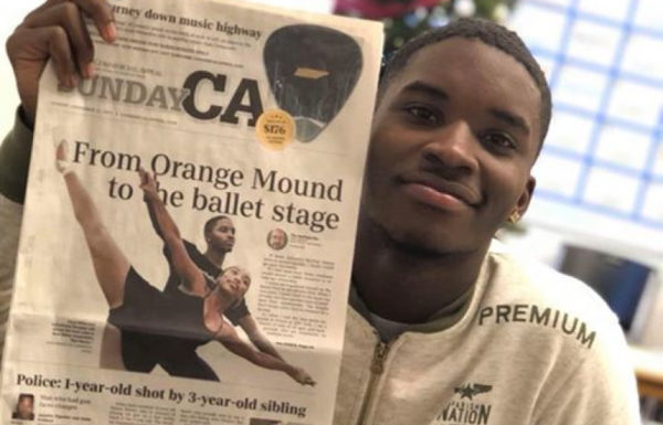 young man holding up newspaper
