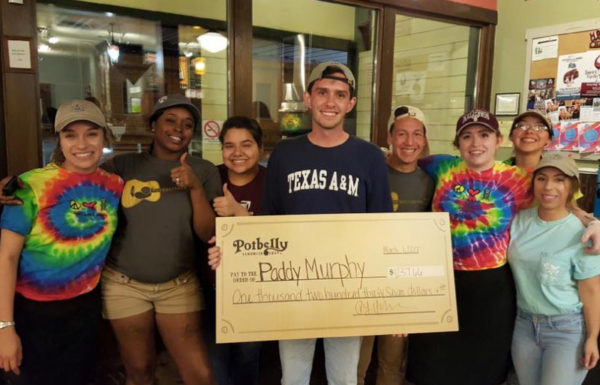 college students holding fundraising check