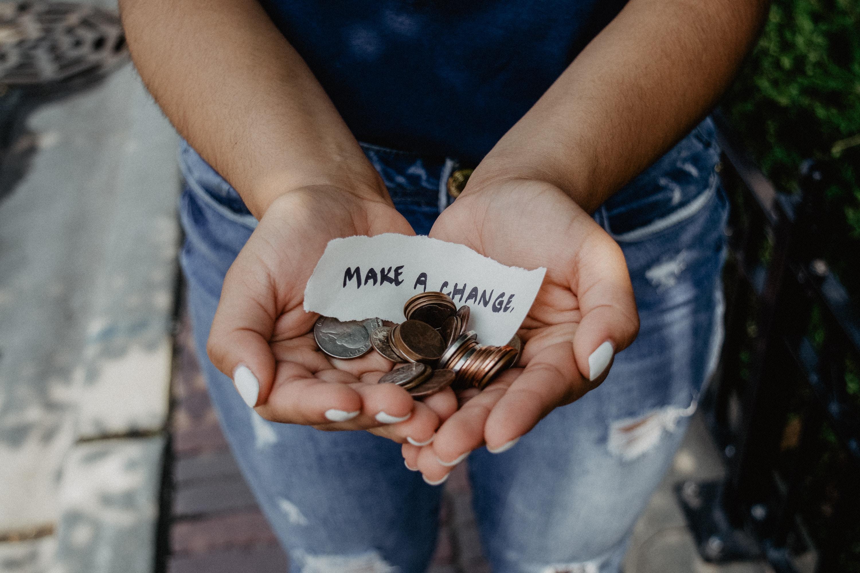 """Person zeigt seine Hände mit Münzen und Zettel """"Make a change"""""""