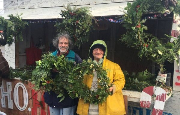 men holding holiday wreaths