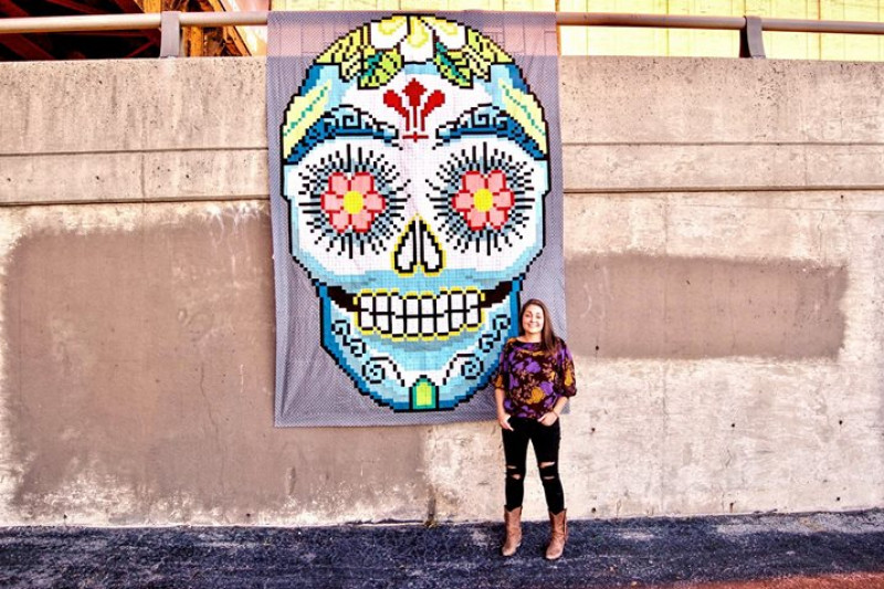 Woman in front of a Day of the Dead quilt