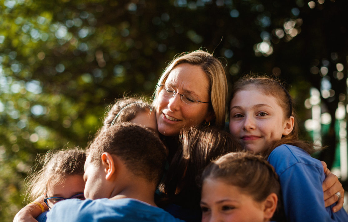 A woman hugging five children