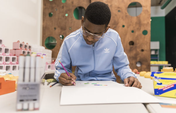 A young man drawing at a school table.