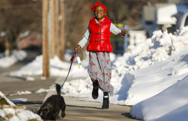 young girl walking dog in snow