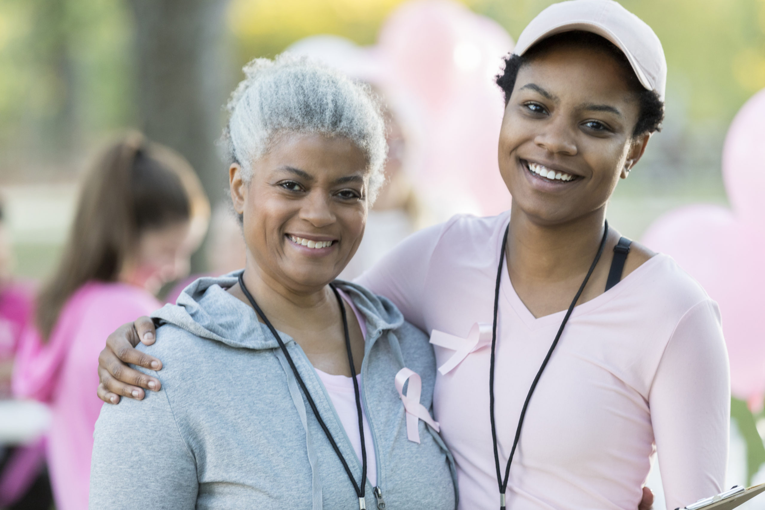 Senior woman and daughter smile for camera at race for cure