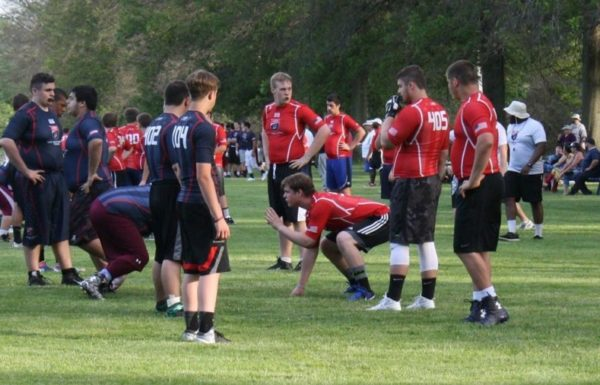 A group of football players on the field at a USA football camp