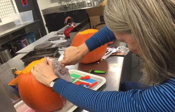 A woman with blonde hair carving a pumpkin