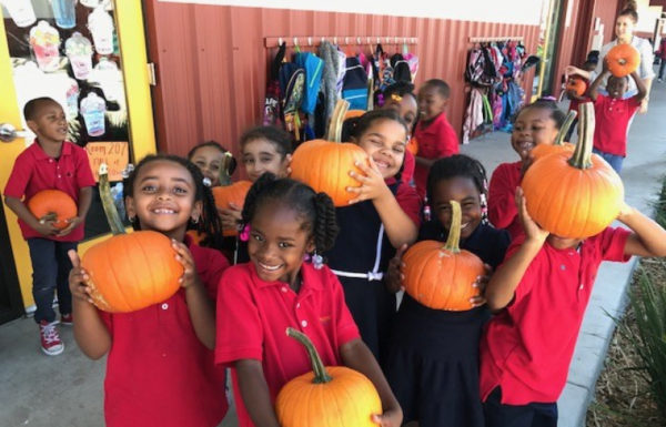 A group of of school children holding pumpkins and smiling.