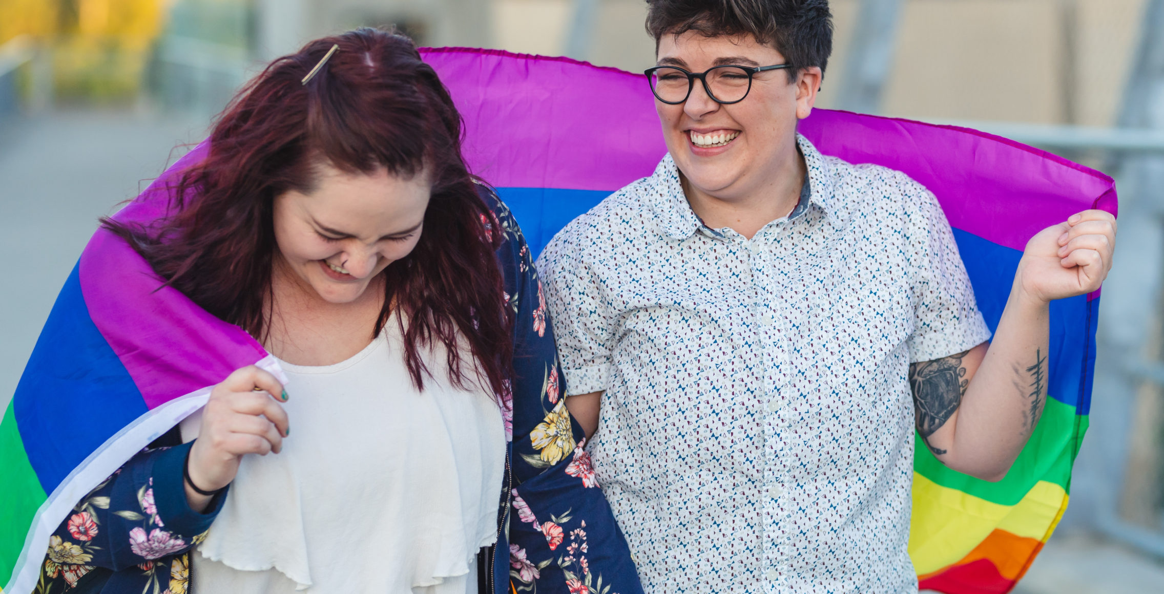 Two women laugh and carry the Pride Flag over their shoulders
