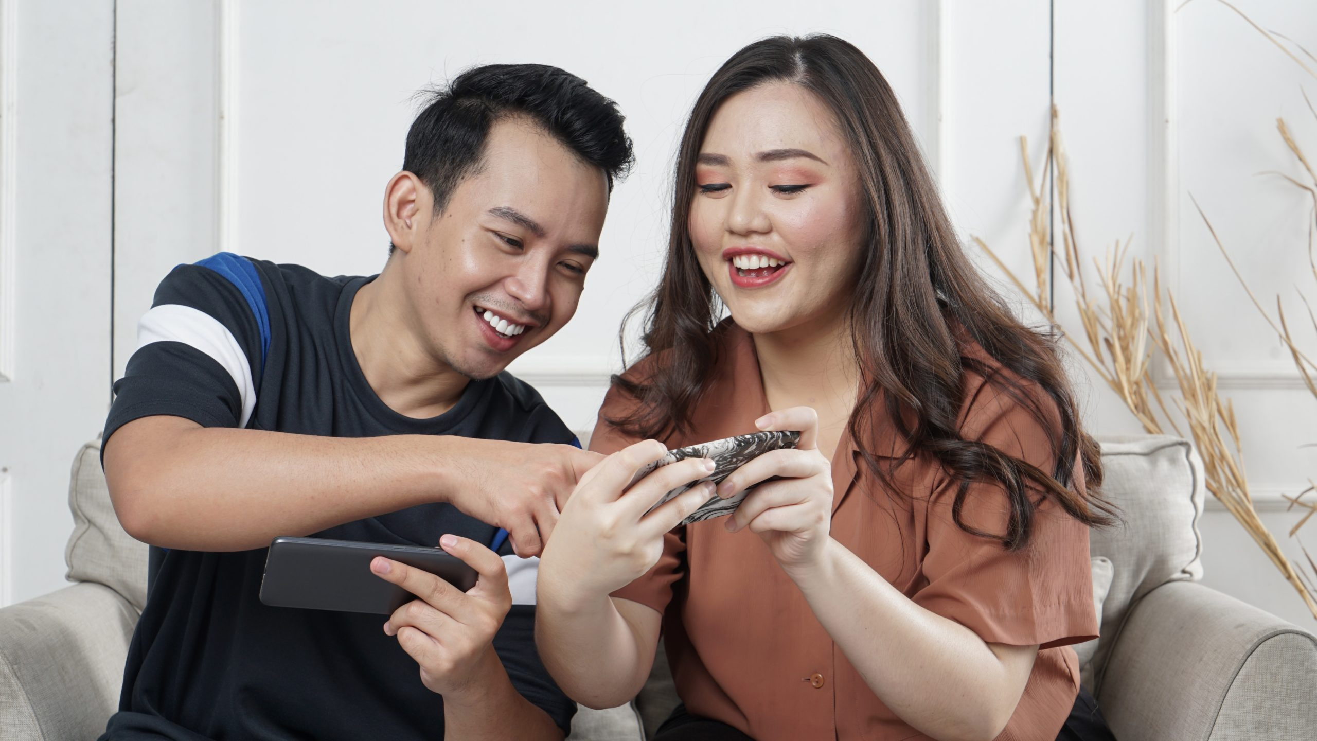 A young man and woman laughing at their phones