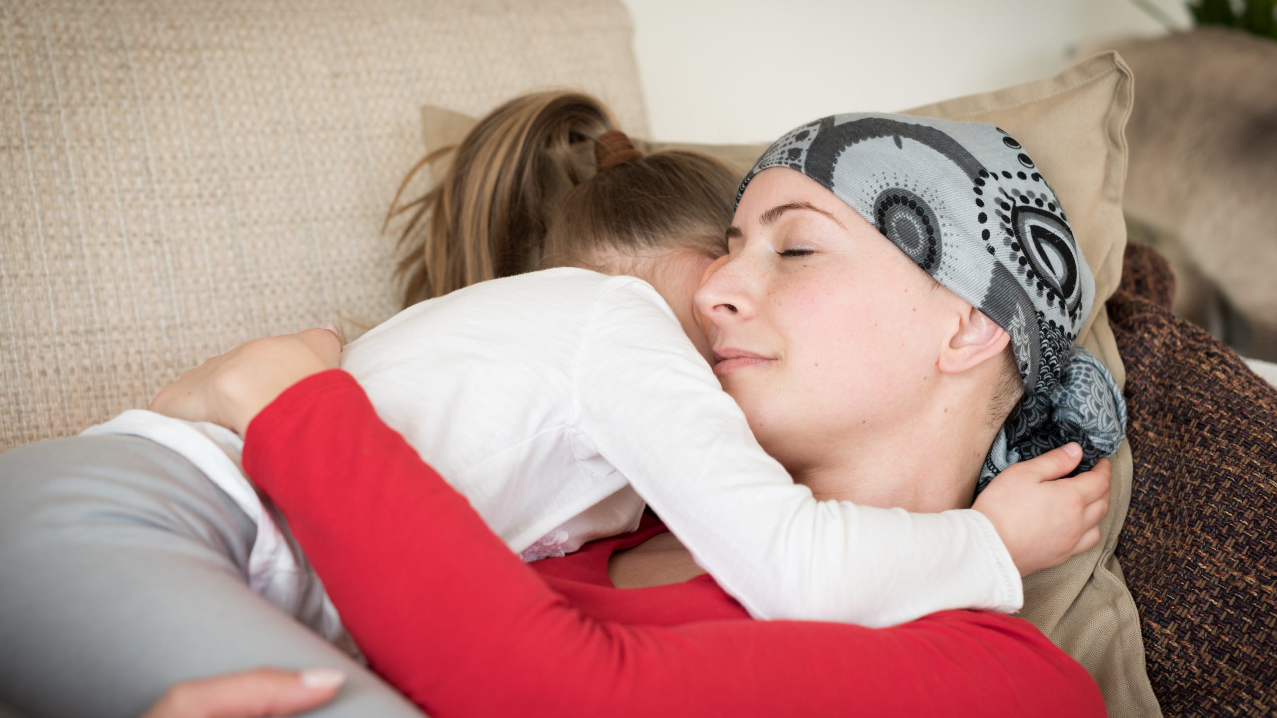 Young adult female cancer patient spending time with her daughter at home, relaxing on the couch.