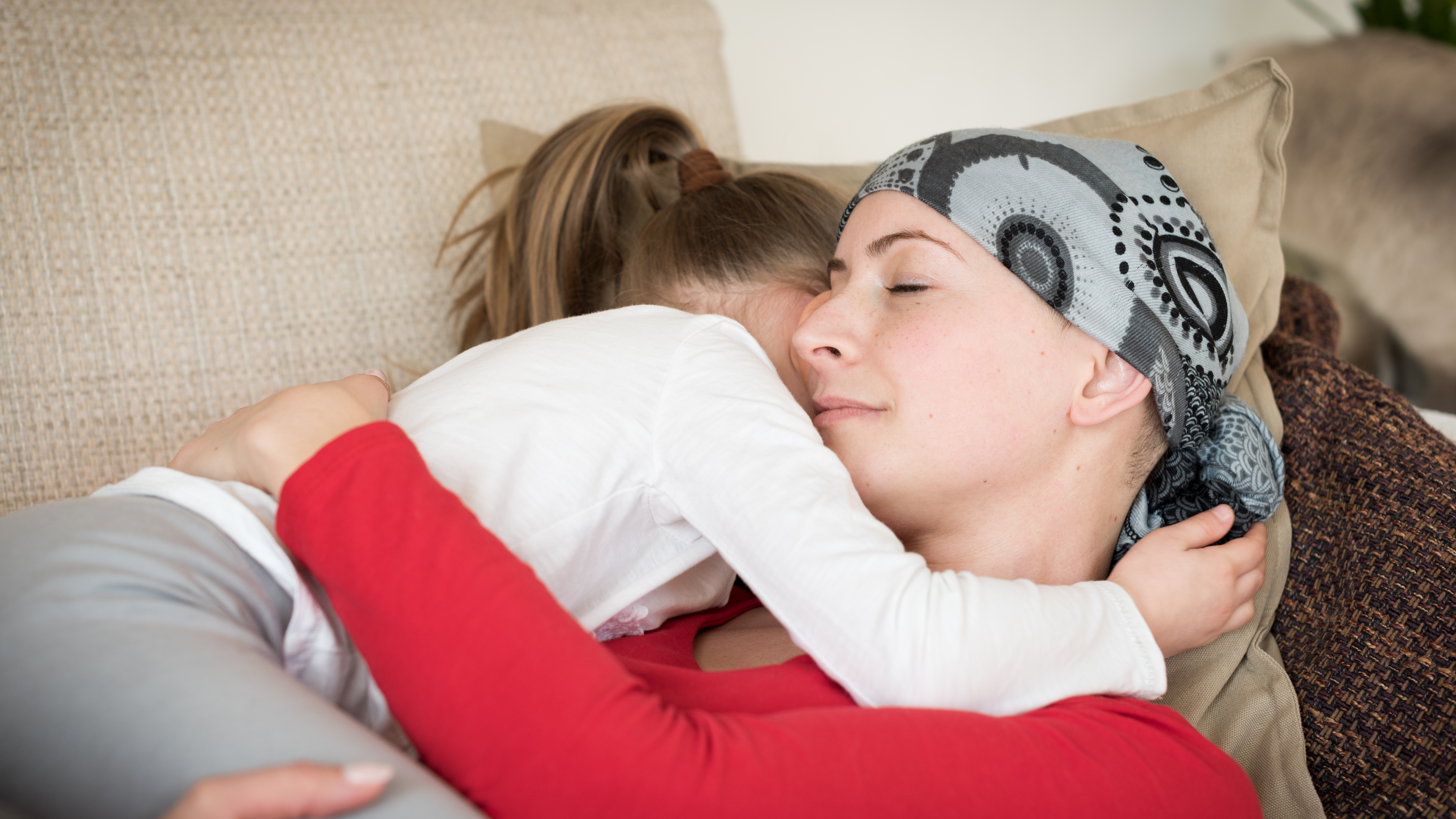 Young adult female cancer patient spending time with her daughter at home, relaxing on the couch. Cancer and family support concept.