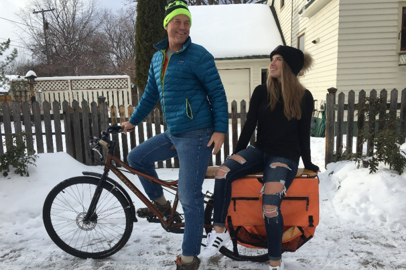 young couple sitting on a bike in the snow