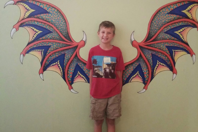 young boy posing in front of dragon wings painted on a wall