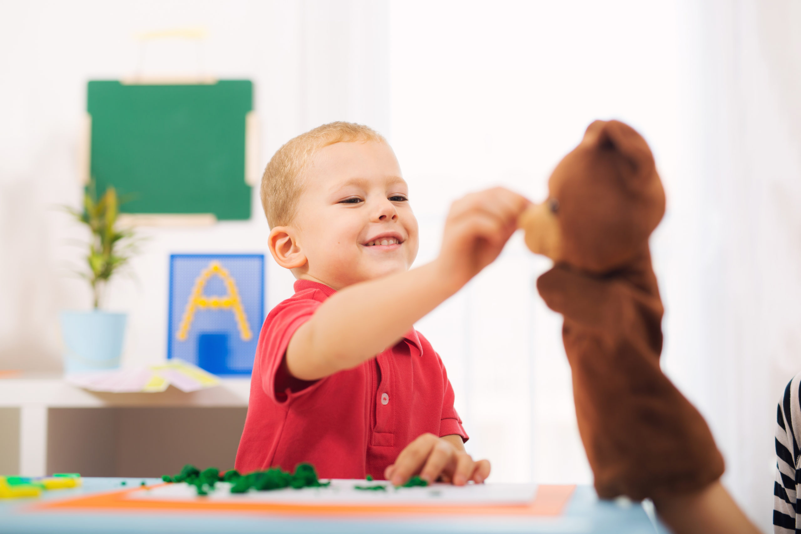 Little boy during lesson playing with a bear puppet