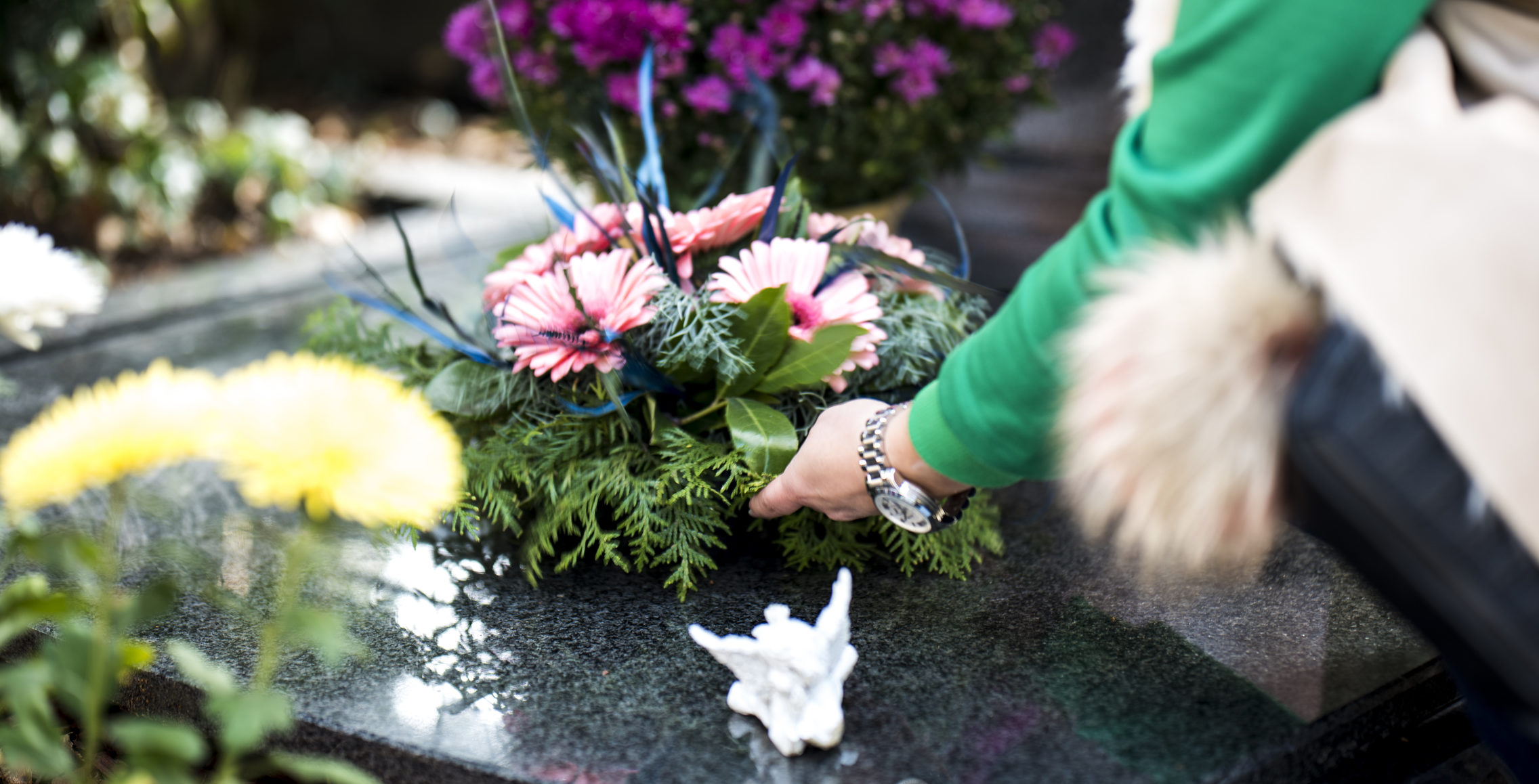 Woman's hand putting some flowers on a grave