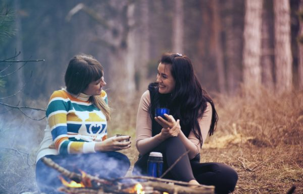 two women talking next to a campfire