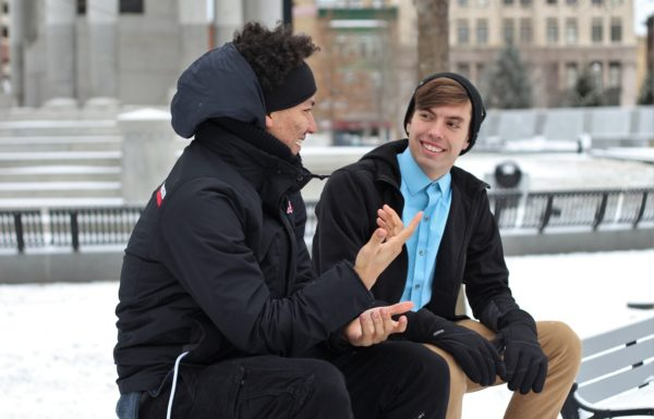 two men sitting and talking on a bench in winter