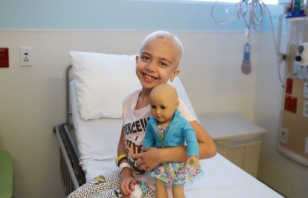 young girl with cancer posing with doll in hospital bed