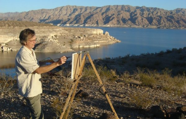 a man paints a nature scene near a lake