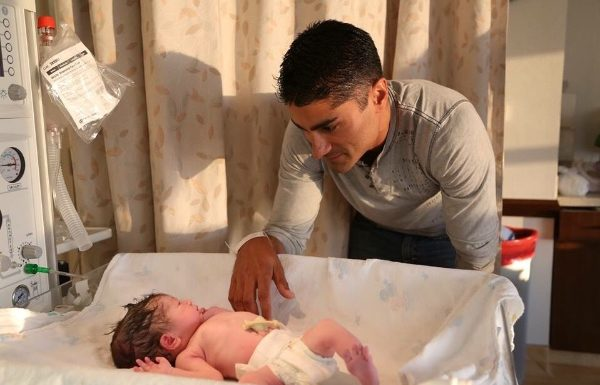 young adult father with his newborn in hospital