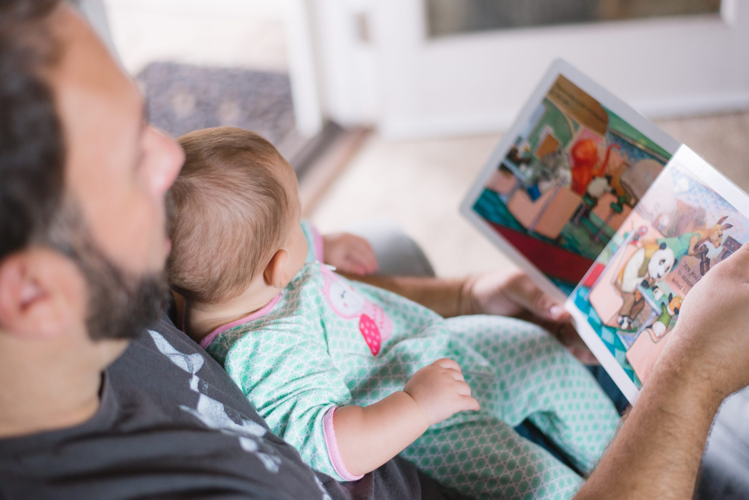 father reading children's book to baby on chair
